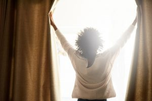Rearview shot of a woman opening the curtains on a bright sunny day