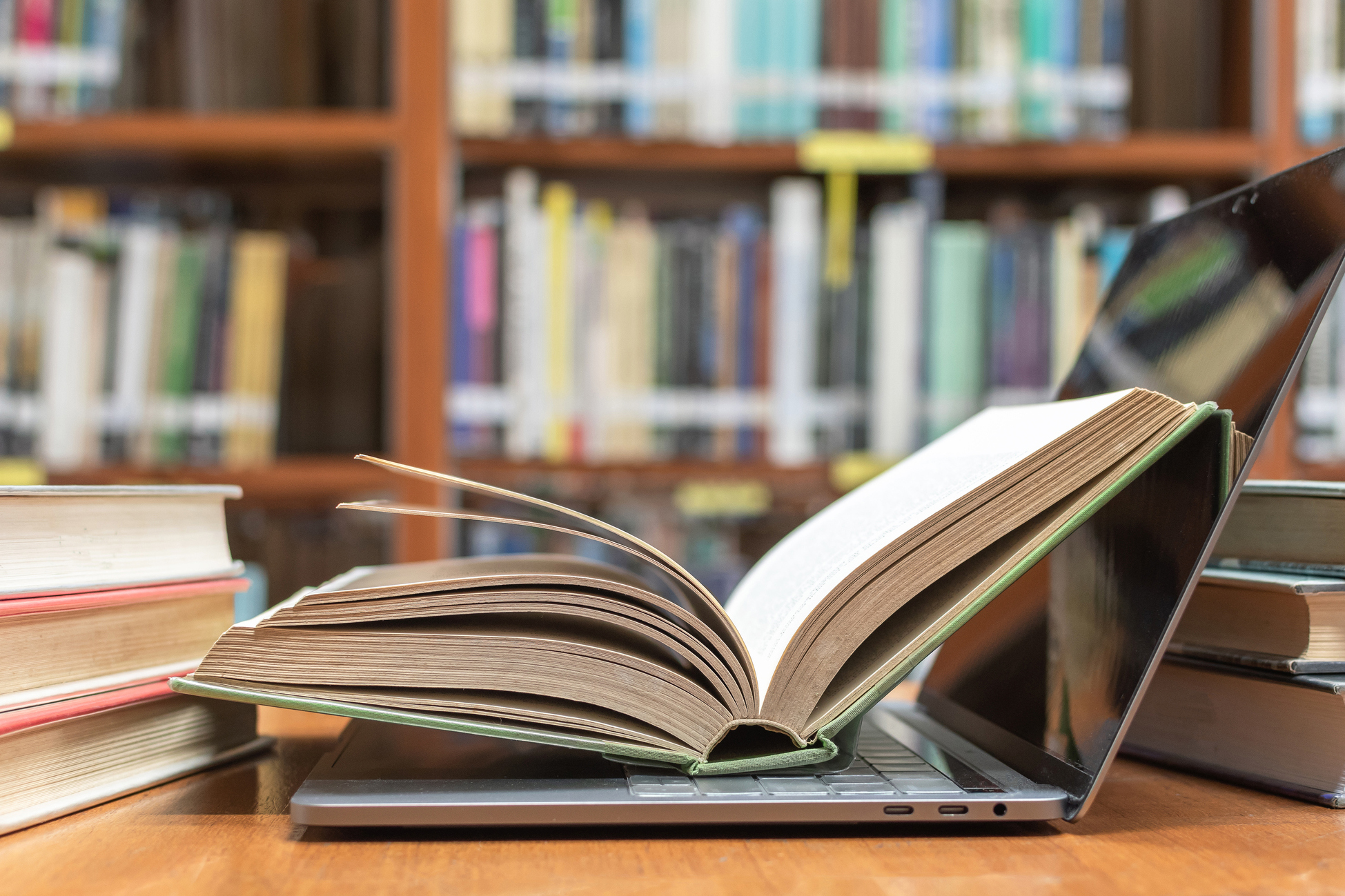 E-learning class and e-book digital technology in education concept with pc computer notebook open in blur school library or classroom background among old stacks of book, textbook archive collection