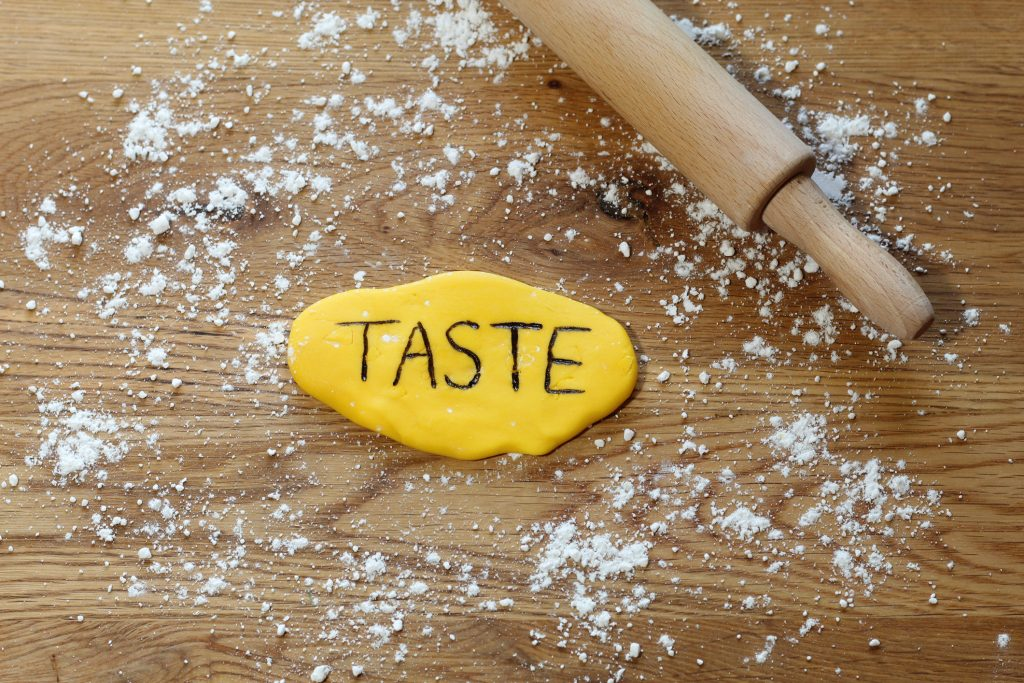 The word 'taste' written in yellow rolled icing using edible pens. Taken in the UK.